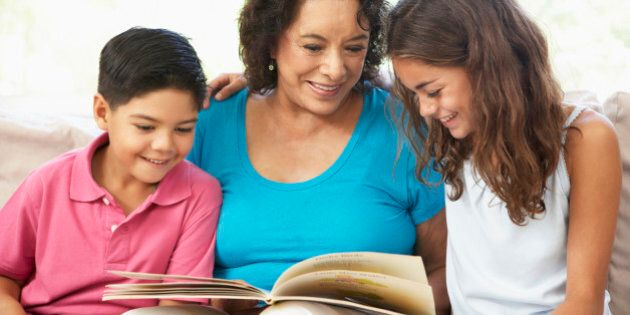 Grandmother Reading With Grandchildren At Home
