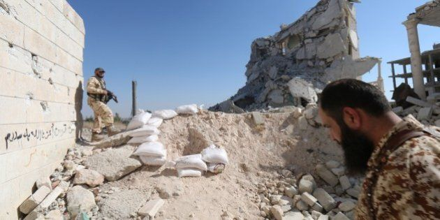 Rebel fighters walk on the rubble of destroyed buildings at a former research centre being used as a...
