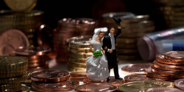 Miniature wedding couple figurines amidst stacks of European Union coins