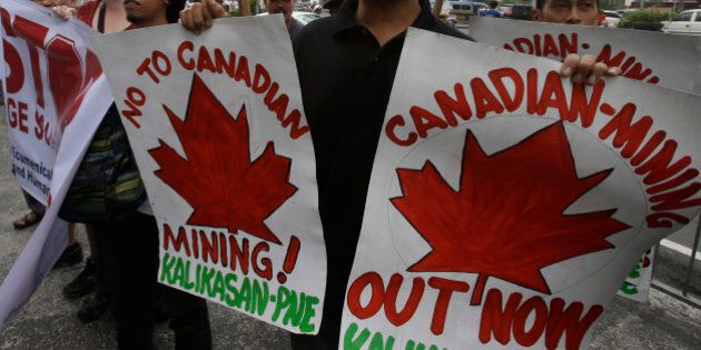 Protesters display placards as they picket the Canadian Embassy to coincide with the official visit of...