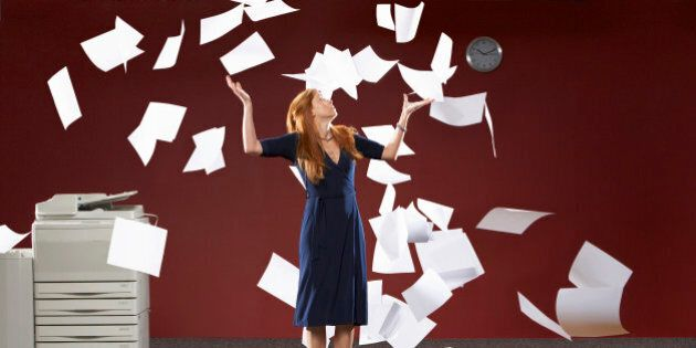 Woman throwing sheets of papers in