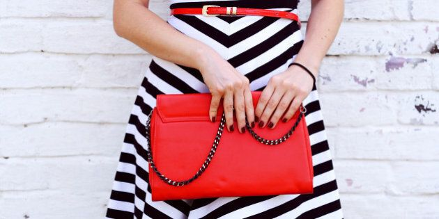 Outdoor Fashionable girl near white street wall .Marine and retro style. striped dress with red handbag