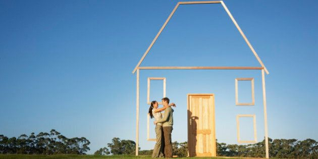 Couple hugging next to vertical house