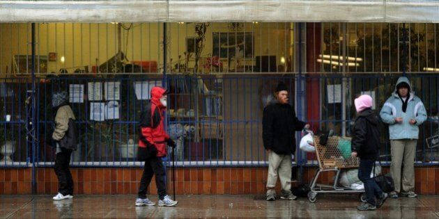 A group of homeless and poor seek shelter from the rain outside a store in the Downtown Eastside area...