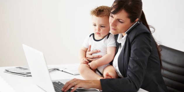 Working mom talking on the phone while holding a baby and typing on her