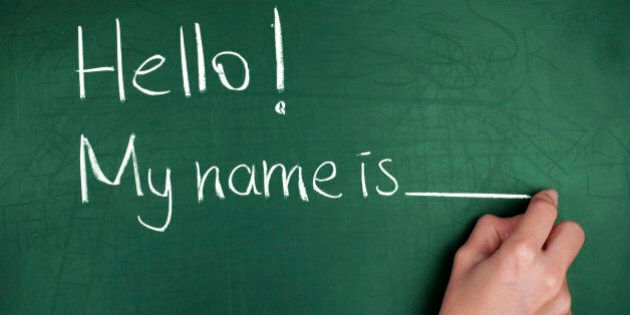 Woman hand writing ' Hello! My name is... ' on green