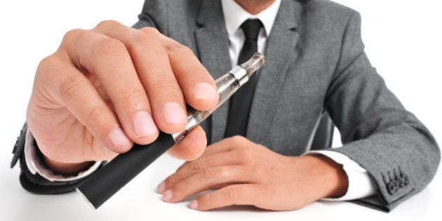 man wearing a suit vaping