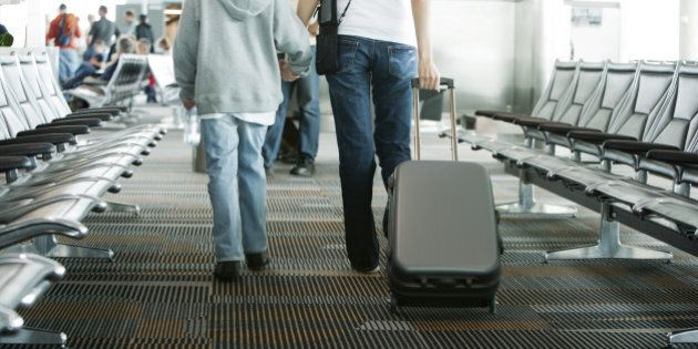 Mother and son walking in airport, mother pulling suitcase, rear