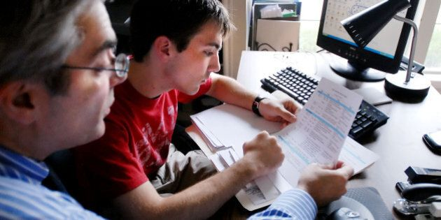 Chris Economou, left, a financial planner, goes over college paperwork with son Thane 18, in their home...