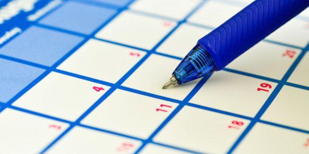 Close-up of an office calendar and a pen.