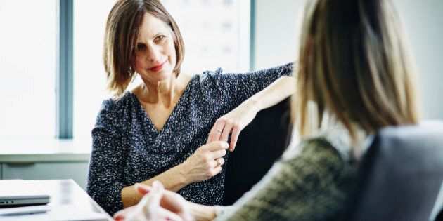 Mature businesswoman in discussion with female colleague at conference table in