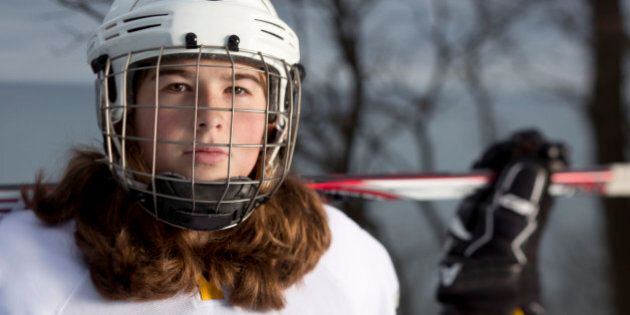 Eleven year old girl hockey player portrait on an ice rink overlooking Lake Michigan in