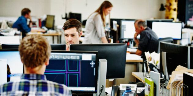 Architects working on computer aided design projects at workstations in office