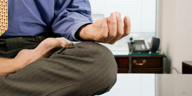 Businessman meditating barefoot on