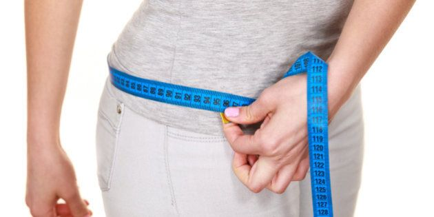 Weight loss. Woman fit girl measuring her hips with blue measure tape closeup. Part of female body side...