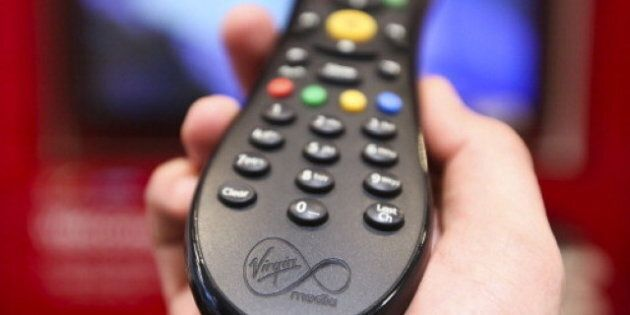 A man holds a television remote control unit for a Virgin Media set top box in this arranged photograph...