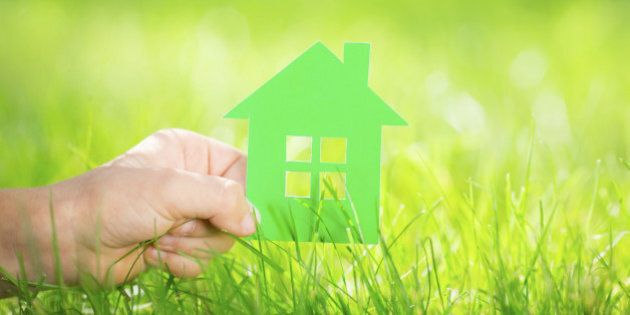 Paper house in children`s hand against green spring background. Real estate