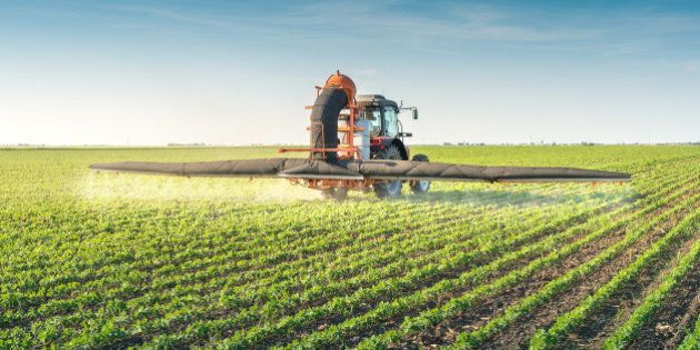 tractor spraying pesticides on soy