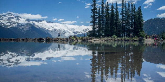Reflections of trees and snow covered mountain on Garibaldi
