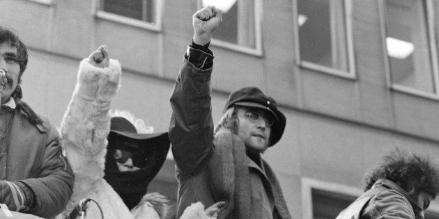 John Lennon and his wife Yoko Ono raise their fists as they join a protest, Feb. 5, 1972, by about 500 persons in front of British Overseas Airways Corp. offices in New York on Fifth Avenue.   The demonstrators called for the withdrawal of British troops from Northern Ireland.  (AP Photo/Ron Frehm)