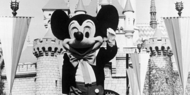 circa 1955: A person in a Mickey Mouse costume at the gate of the Magic Kingdom at the Disneyland theme...