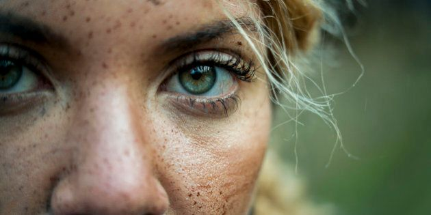 Portrait of a muddy female mountain biker in nature, travel and sports imagery, eyes only, close up looking at camera, landscape composition, one female only aged 25 to 30.