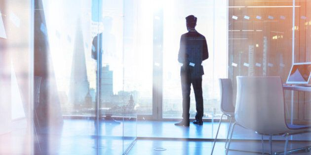 Businessman looking out of office over