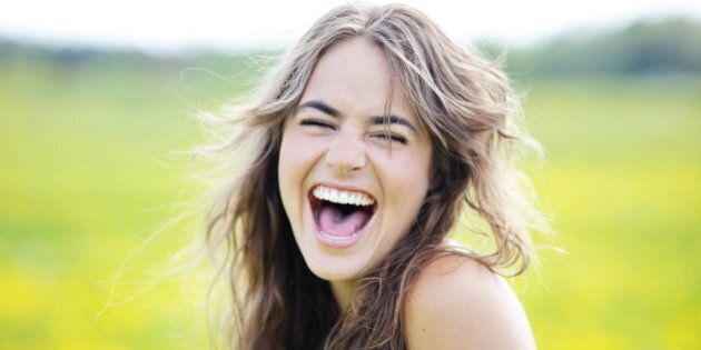 Woman laughing with her eyes closed