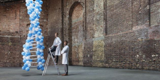Scientists in empty warehouse with ladder standing next to DNA molecule made of balloons