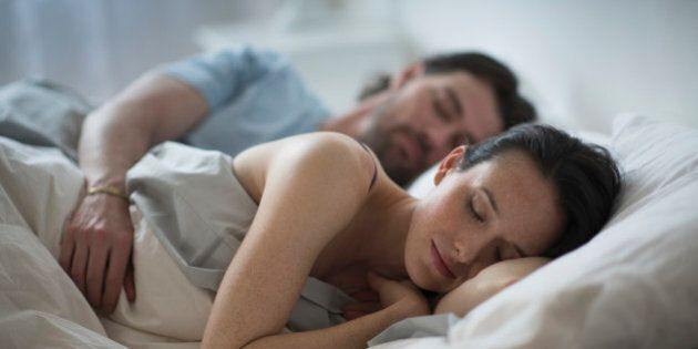 USA, New Jersey, Couple sleeping together in bed at