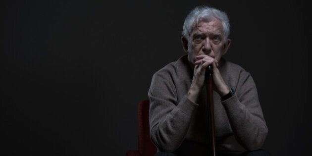 Thoughtful elder man sitting in a dark