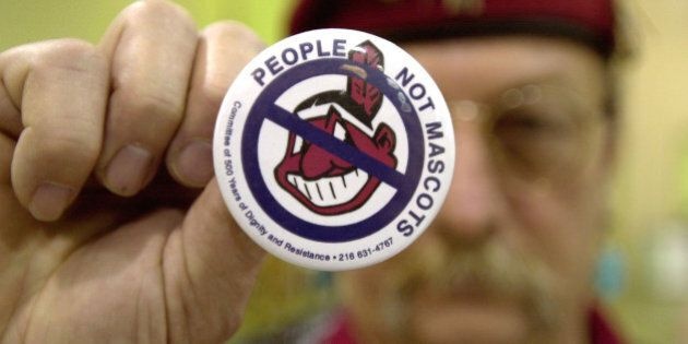 COLUMBUS, OH - JANUARY 1:  Powwow attendee Sonny Hensley holds an anti-mascot button to protest using Indians as mascots for sports teams at the 10th Annual New Years Eve Sobriety Powwow January 1, 2003 in Columbus, Ohio. The Ohio Center for Native American Affairs sponsored the event, attracting people from several U.S. states as well as Canada.  (Photo by Mike Simons/Getty Images)