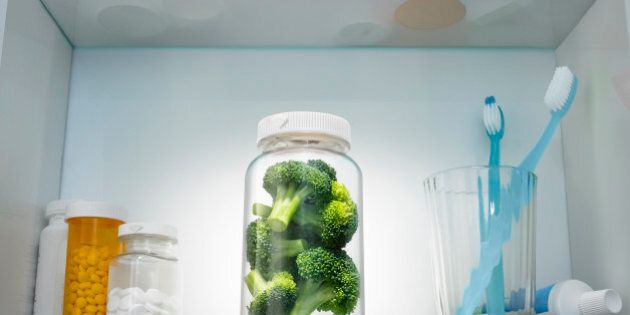 Pieces of broccoli in a pill bottle in a medicine cabinet. The image was is a staged set built and designed...