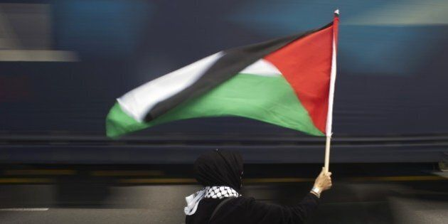 A woman holds a Palestinian flag as a truck passes by, during a protest against Grammy-winning American...