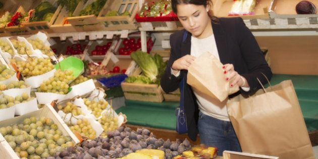 Young woman in a grocer's shop which chooses and buys fruits. She is filling a