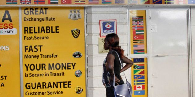 A woman looks at the closed doors of a money-transfer service in Nairobi, Kenya Wednesday, April 8, 2015. The Kenya government said Wednesday that it was freezing the accounts of a list of companies and individuals identified because of suspicious transactions, with the list including some money-transfer services dealing in remittances to Somalia. (AP Photo/Khalil Senosi)