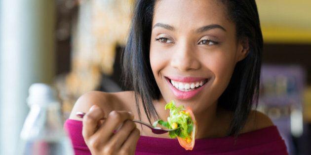 Closeup shot of young woman eating fresh salad at restaurant. Healthy african girl eating salad and looking...