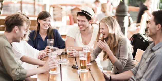 Group of young cheerful people having fun drinking beer