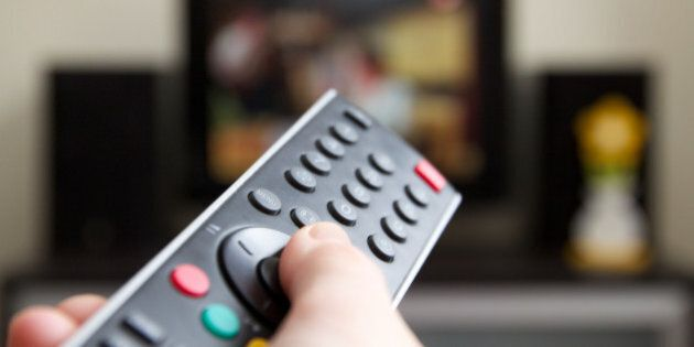 Human hand holding remote control changing Channels with television