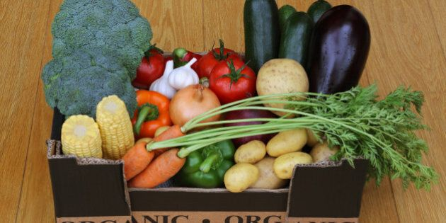 Box filled with organic vegetables, carrots, aubergine, courgettes, tomatoes, pototoes, onions, garlic, peppers, broccoli and corn on the cob, on wooden floor.