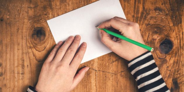 Woman writing recipient address on mailing envelope, female hands from above on office desk sending letter,...