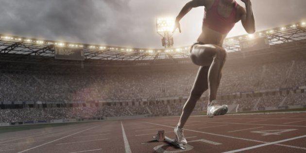 female athlete bursting out of blocks on athletics track in full floodlit stadium under dramatic sky