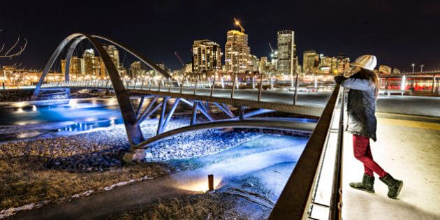 Women enjoys a view of Calgary at night from the George C. King