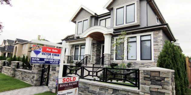 Realtors' signs are hung outside a newly sold property in a Vancouver, B.C., Canada neighbourhood where...