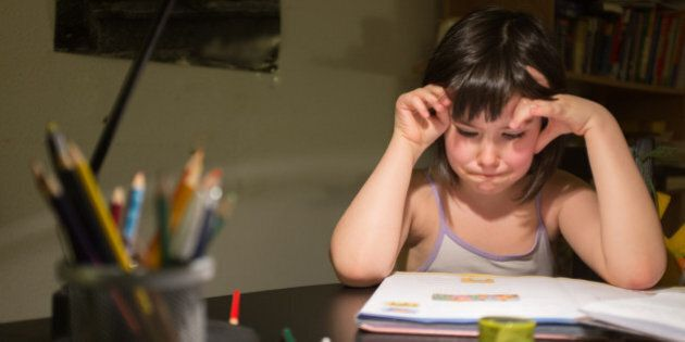 little girl at the table looking a little frustrated at her exercise book.