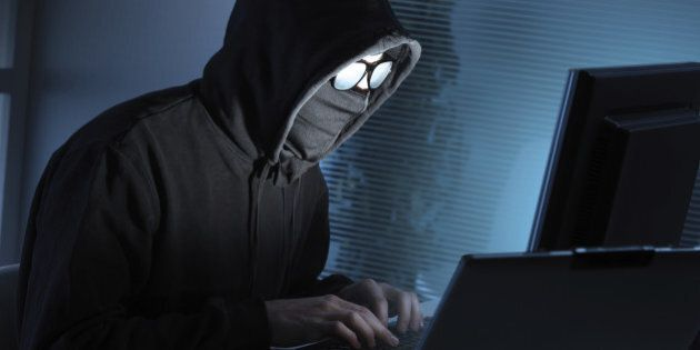 Young male thief stealing data from computer