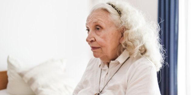 Lonesome senior woman sitting at her bed in retirement