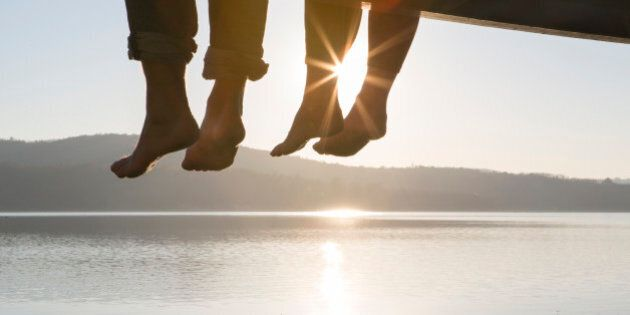 Couple's feet dangle from dock,above tranquil
