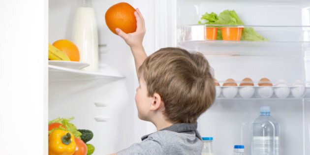 Little cute boy picking orange from fridge. Vegetables and fruits in the