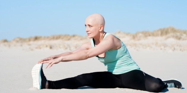 Young beautiful woman is stretching on the beach after enduring chemotherapy because of